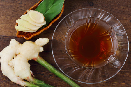 pain: Top view of ginger juice and fresh ginger with green leaves isolated on wooden background.