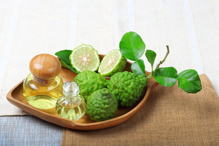 Kaffir lime or bergamot with aromatic spa of bottles essential oil on sack background.