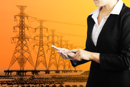 electricity export: Businesswoman holding phone with high voltage electric transmission tower energy pylon background, Industry energy business concept. Stock Photo