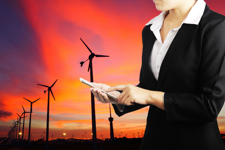 electricity export: Businesswoman holding phone with wind turbine generator electricity background, Industry energy business concept. Stock Photo