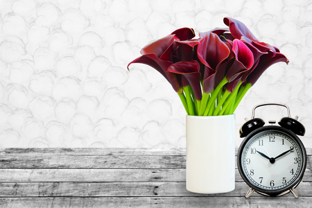 Flowers of dark red calla lily and clock on wood vintage background, image for design and other. Stock Photo