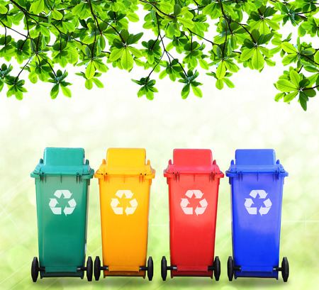 Red yellow blue and green bins on nature background, image for design and other. Stock Photo