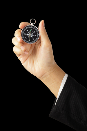 Businesswoman hand holding vintage retro compass isolated on black  , Instrument that indicates magnetic north.