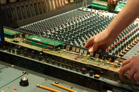 computerize: technician working on audio mixing console