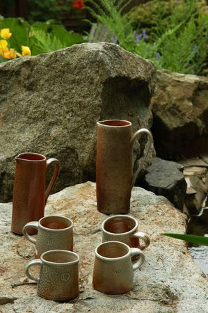 clay cup and pitcher decorated in garden