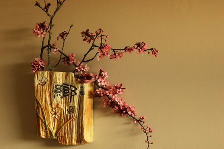 plum blossom in vase on the wall