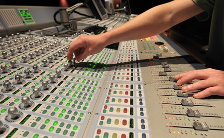 Audio engineer operating mixing console with hands photo