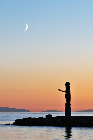 crescent: Totem pole and crescent moon at Ambleside beach in North Vancouver