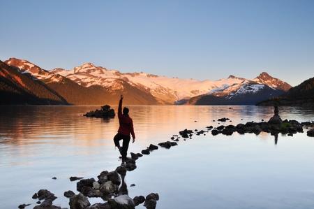 分散のヨガの女の子ロック、ガリバルディ湖の夕日 写真素材