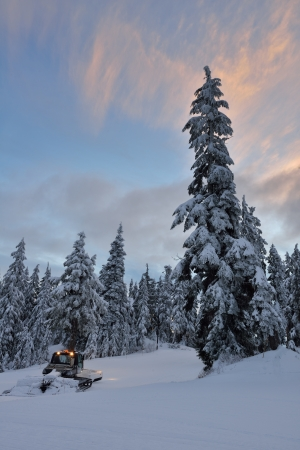 groomer: Mt  Seymour ski resort in the early morning, a snow groomer on the slope Stock Photo