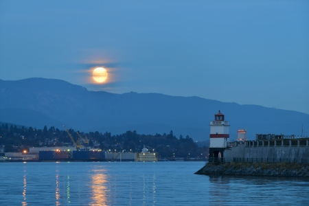 Harvest Moon and brockton point Lighthouse in Stanley Park Stock Photo