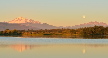 three sisters: Full Blue Moon over Mt. Baker and Three Sisters Mountain, from Wiser Lake, Washington Stock Photo