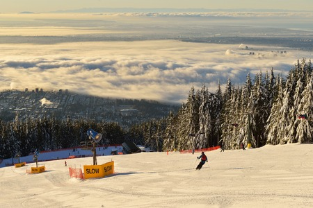 foggy hill: Grouse Mountain Ski Hill with foggy cityscape beneath, Vancouver, BC Stock Photo