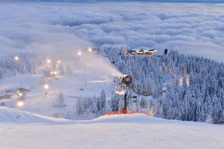 foggy hill: Grouse Mountain Ski Hill with foggy cityscape beneath at sunset, Vancouver, BC