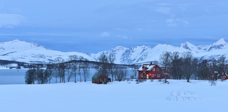 farmhouses: Red farmhouses in Tromso with the mountains on Kvaloya, Northern Norway