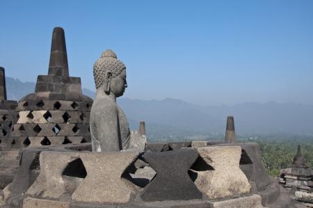Buddha statue. Mountain on background. Borobudur. Java. Indonesia photo
