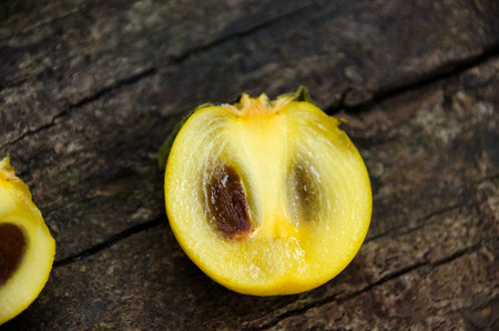 Fruit in the persimmons family in Thailand. Persimmon cut  half on top of natural wood.