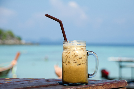 Cold coffee on wooden table and sea background Stock Photo