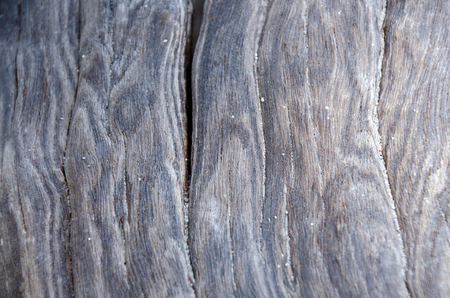 Tropical hardwood and textured background. Abstract background. Close up weathered wooden board and sand outdoors background. Natural texture. Old wood and sand texture. Untreated knotty wood.