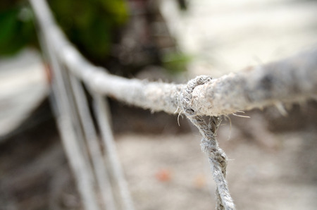 Close-up of rope knot line tied together with bridge background. White rope tied in a knot for adventure.Rope, tie a knot tied to a mesh of metal poles for children to climb. Stock Photo