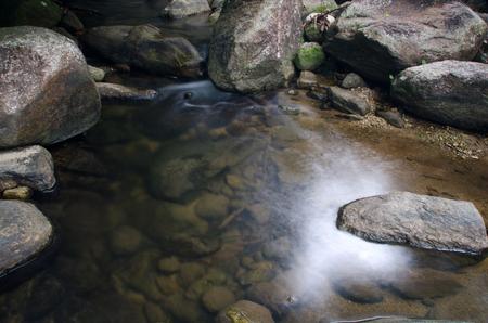 Waterfall with stone of green moss in rain forest , Kiriwong Village, kamloan, Lansaka, Nakhon Si Thammarat, Thailand.