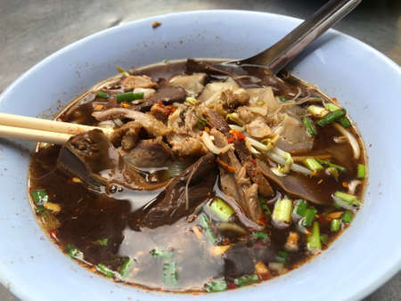 Close up Duck noodle on bowl, vice tray and food,One of the menu of Thai noodles that foreigners have to taste, china town, Thailand (Real from the Street food)