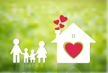 Happy family at home, mom and dad holding hands with boys and girls. Home heart on the ground, blurred green background.