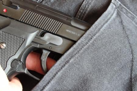 Person zieht Pistole aus der Hosentasche einer Jeans