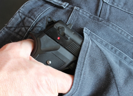 Mann zieht Pistole aus der Hosentasche einer Jeans
