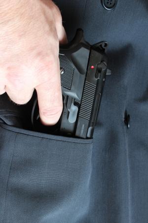Mann zieht Pistole aus der Tasche einer Anzugsjacke