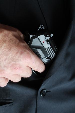 mann: Mann zieht Pistole aus einem Anzug heraus