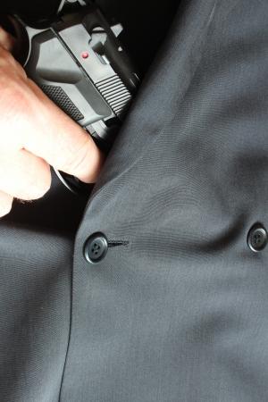 Mann zieht Pistole aus einem Anzug heraus