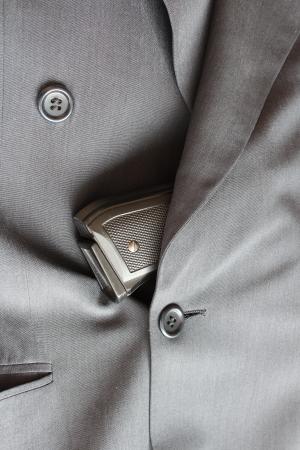 Pistole steckt in einem Anzug