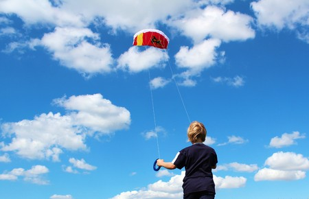 Boy is playing with stuntkite under blue sky photo
