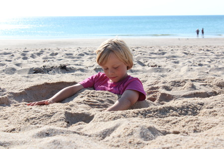 child sitting buried in the sand