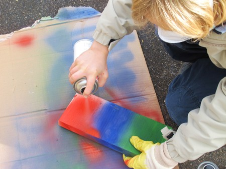 propellant: child sprayes on wood Stock Photo