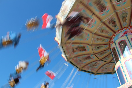 carousel in motion in closeup in front of blue sky photo