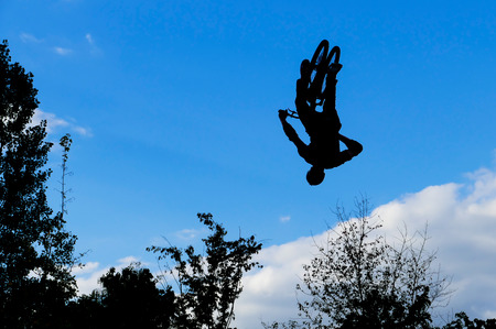 somersault: Mountain biker jumps through the air and makes somersault