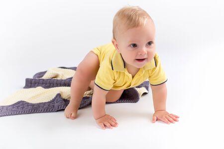 Chico lindo niño arrastrándose sobre la manta de rayas de doble color sobre el fondo blanco.