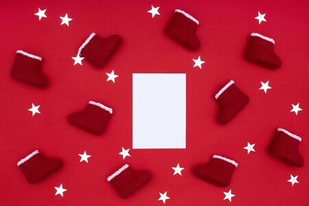 Flat lay of a postcard with red Santa boots decorated with white fur and shiny silver stars on the red paper background Stockfoto