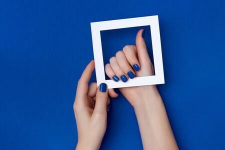Composition of women's hands with nails in classic blue color Stock Photo