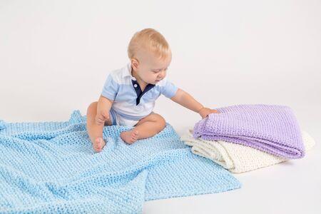 Niño con mantas de felpa de colores sobre el fondo blanco.