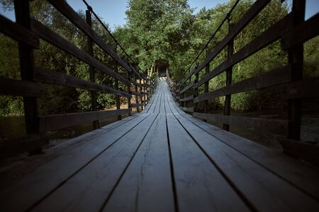 Old wooden bridge leading into green trees over the river Stockfoto
