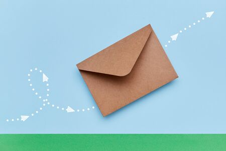Craft brown envelope flying above green paper ground with indicated direction by white points and arrows depicted with drawn airplanes. Mail concept