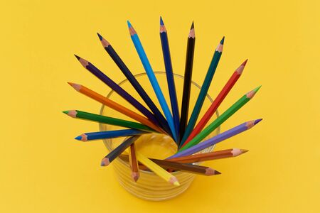 Composition of many multicolor pencils on the yellow background Stock Photo