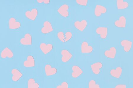 Pattern of pink paper hearts and one broken heart among them on the blue background Stock Photo