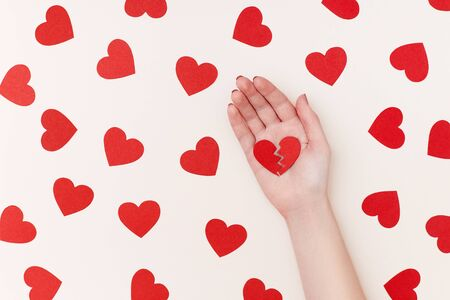 Pattern of red paper hearts surrounding womans hand holding two parts of broken heart on the biege background Stock Photo