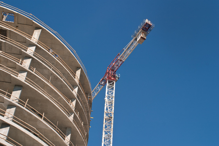Tower crane and a building under construction against the blue sky