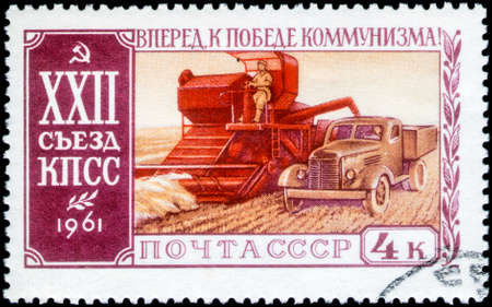 Saint Petersburg, Russia - March 15, 2020: Stamp issued in the Soviet Union with the image of the Combine-harvester and truck. From the series on 22nd Communist Party Congress, circa 1961 Publikacyjne