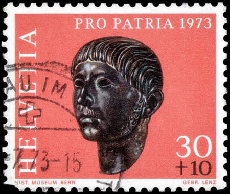 Saint Petersburg, Russia - May 17, 2020: Stamp printed in the Switzerland with the image of the Gallic head from Prilly, Roman Age, circa 1973 Editorial